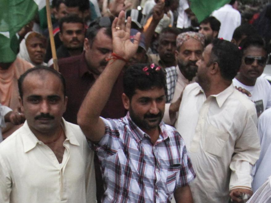 Uzair Baloch (center), 32, controls an impoverished section of Karachi and commands a large armed force. He is routinely described as a gangster, though he calls himself a politician and a social worker. He's shown here at a rally in Karachi in November 2