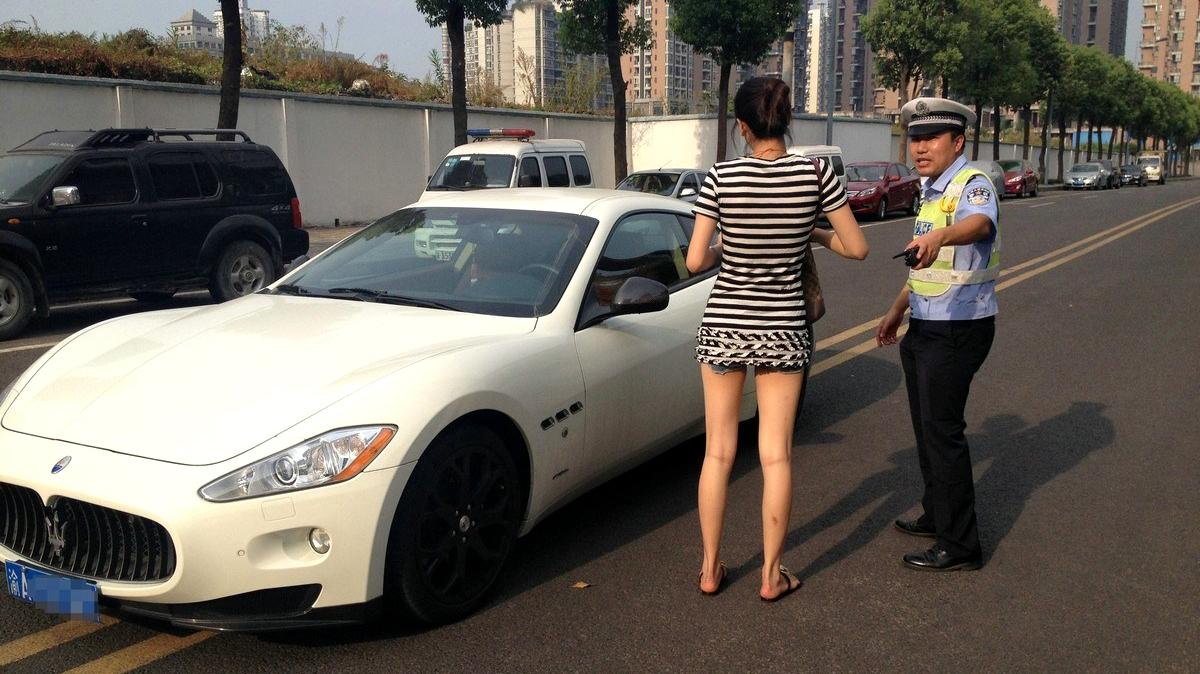 A police officer tickets a young woman for parking a Maserati (estimated to be worth more than $300,000) on the double yellow lines in the middle of the street in Chongqing, China. Stories like this one that go viral in China are increasingly available to