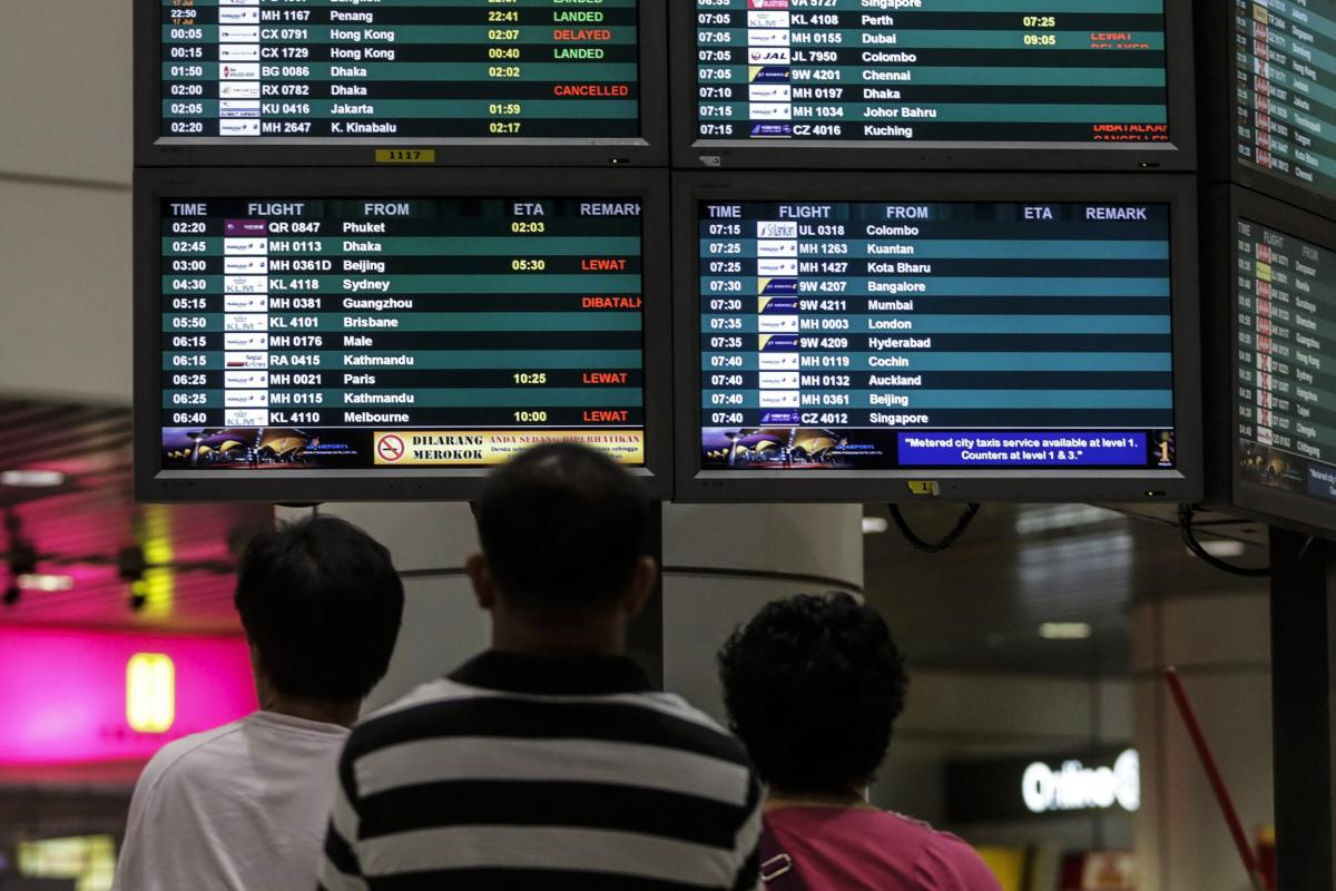 "Passengers at Kuala Lumpur International Airport look at a flight information board. ""Our thoughts and prayers are with those on board the Malaysia Airlines airplane lost over Ukrainian airspace, as well as their families and loved ones,"" Boeing said in a"