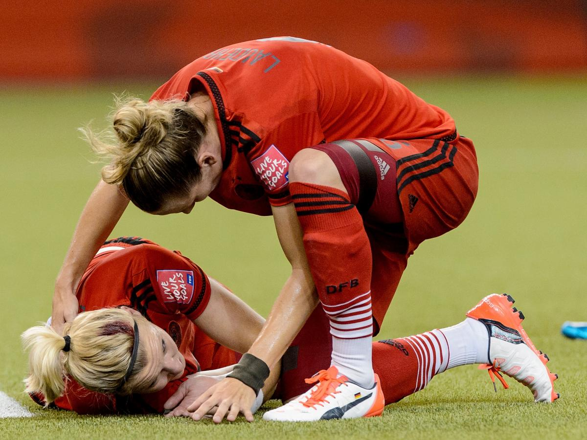 Alexandra Popp of Germany is checked by teammate Simone Laudehr after she and U.S. midfielder Morgan Brian knocked heads during Tuesday night's Women's World Cup semifinal in Montreal.