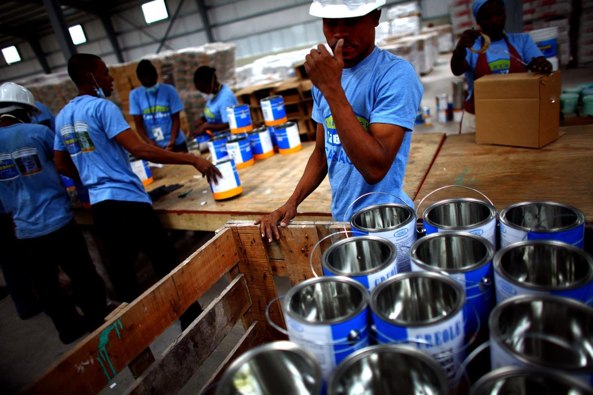 Workers arrange paint buckets before they are filled at a warehouse in the Caracol Industrial Park, which Haiti is billing as the largest in the Caribbean.