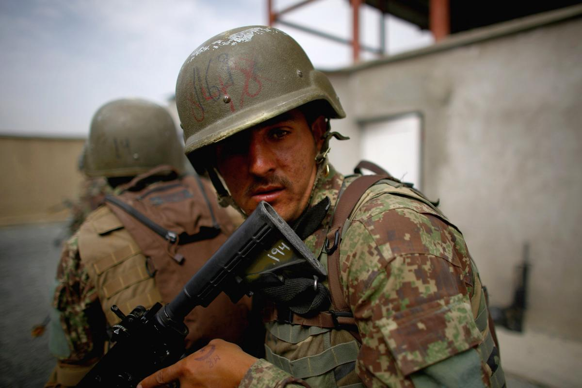 An Afghan commando watches the rear as his squad prepares to enter a shoot house. Wafa joined the Afghan commandos and trained at this very base. The Green Berets took him under their wing while he was there.