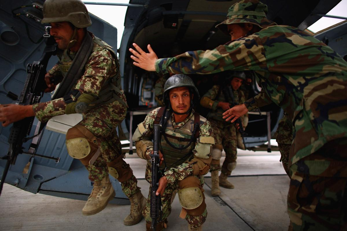 Afghan commandos practice running off a helicopter.