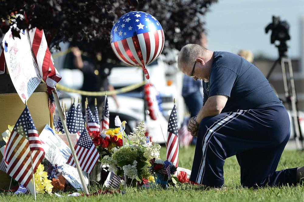 Bill Lettmkuhl kneels by a makeshift memorial near the Armed Forces Career Center on Friday in Chattanooga, Tenn. Mohammod Youssuf Abdulazeez, of Hixson, Tenn., attacked two military facilities on Thursday, in a shooting rampage that killed four Marines.