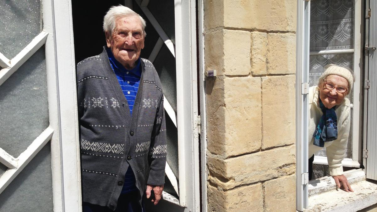 "Lucien (left) and Germaine Rigault lean out of their home in La Cambe, a tiny village in Normandy a short distance from Omaha Beach. The couple, in their 80s, were in La Cambe during the Allied landing on June 6, 1944, and live there still. ""We were scare"