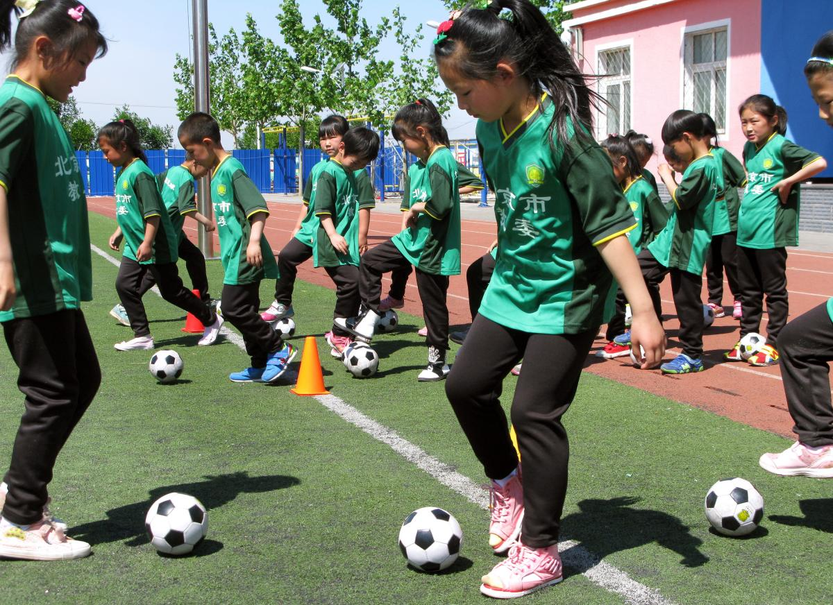 First-graders take soccer class at the Nandulehe Elementary School in suburban Beijing. The school is one of 20,000 that's launching a national soccer curriculum in the next five years. It's part of a government plan to raise China's soccer skills and eve