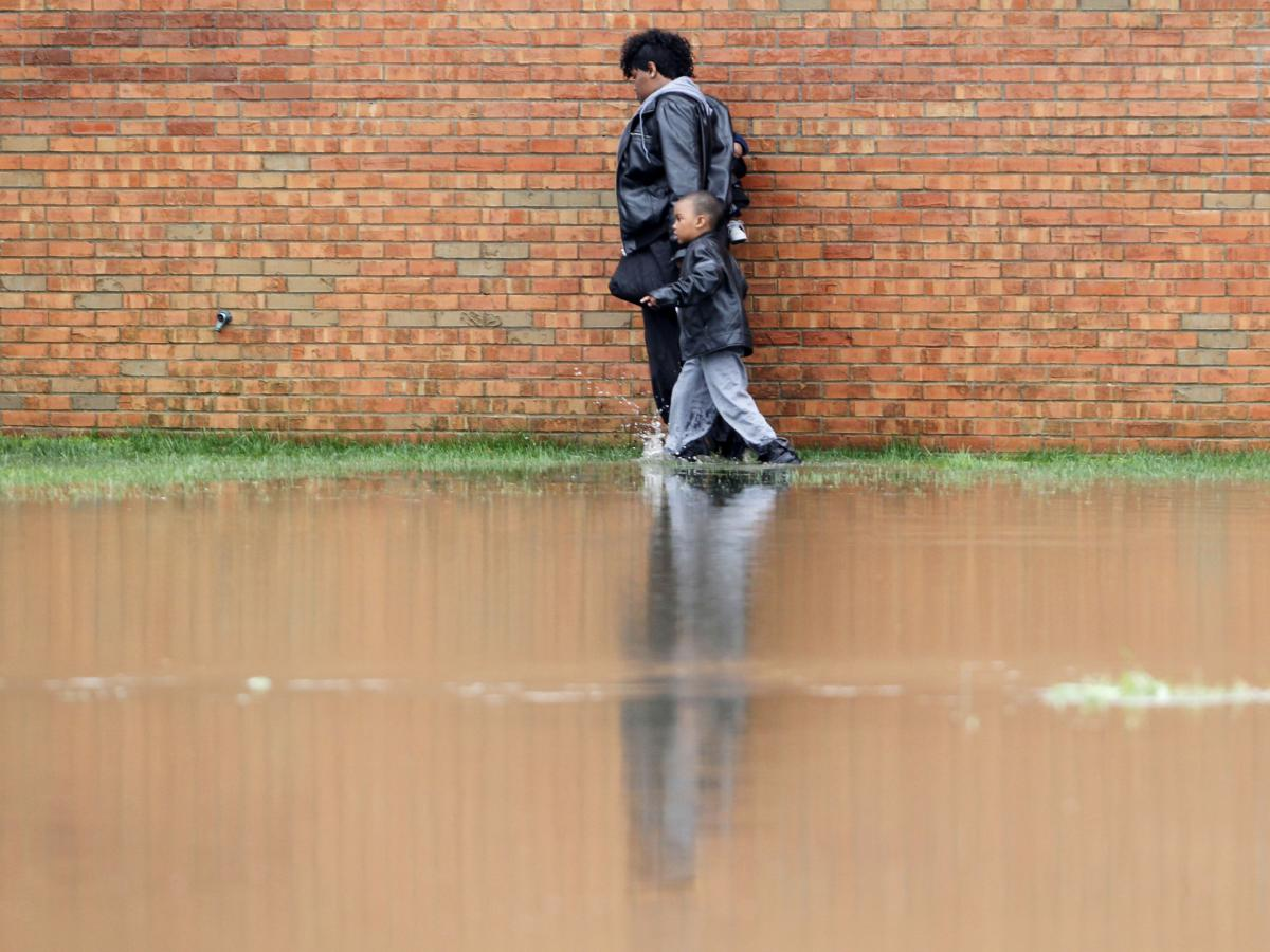 A woman and a young boy walk along a wall of the Guardian Court Apartments as high water forced some to leave their homes after heavy rains of up to seven inches caused flash flooding in Louisville, Kentucky on Friday.