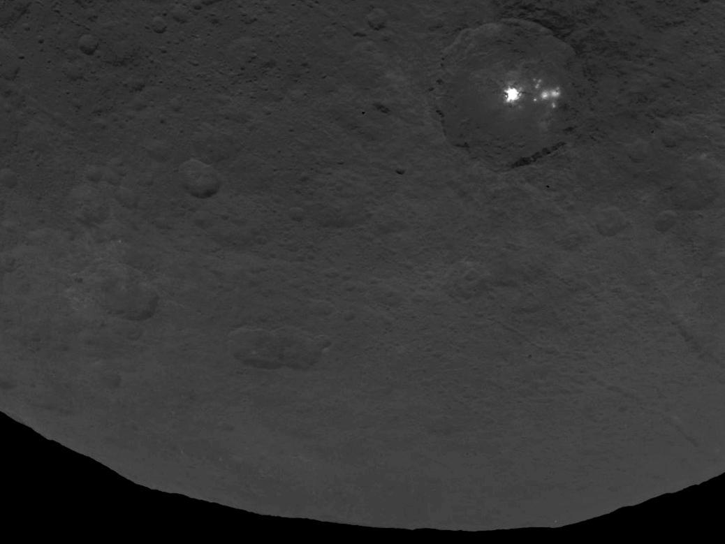 """A """"cluster of mysterious bright spots"""" can be seen on the dwarf planet Ceres, NASA says. The image was taken by the Dawn spacecraft, in orbit of Ceres."""