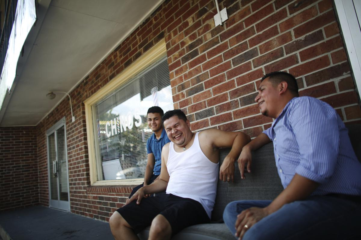 Joel Munguia (center), owner of Chino's, a barbershop in Kenner, La., sits with his nephew, Waldyn Munguia (left), as they have a laugh outside on the waiting benches at the shop. Munguia came to New Orleans from Honduras in 2005 after Katrina and opened