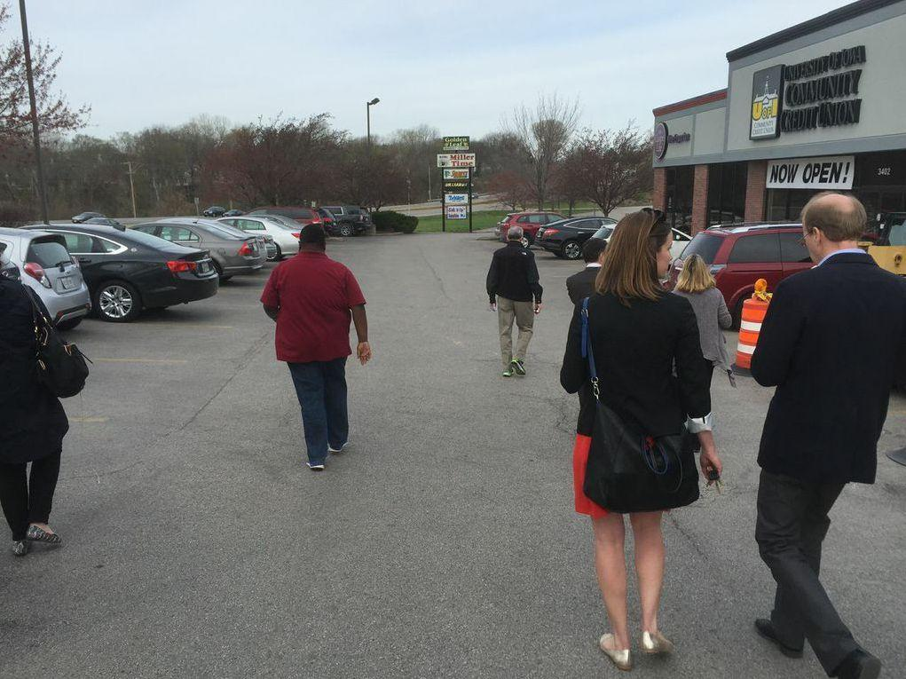 Reporters and campaign staffers rush to their cars to get to Hillary Clinton's first Iowa campaign stop.
