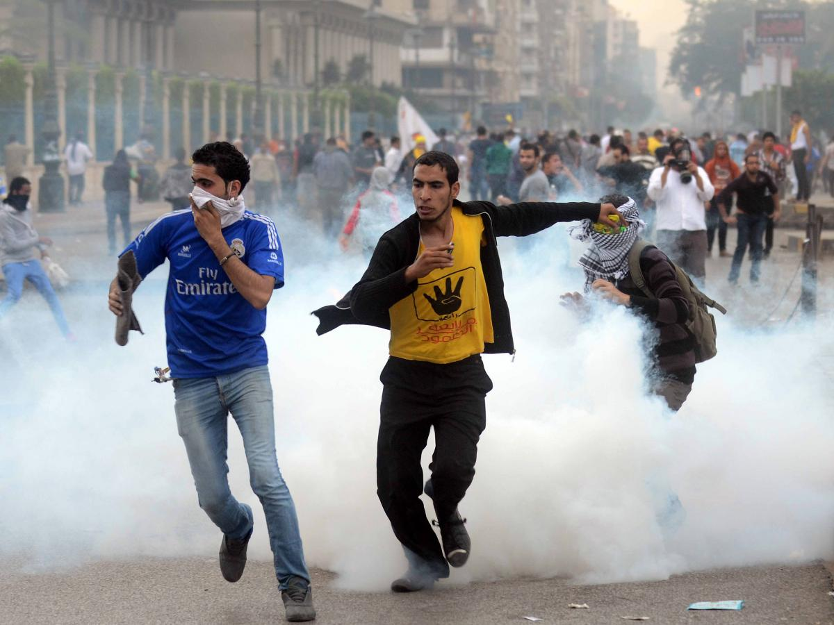 Supporters of the Muslim Brotherhood run from tear gas during clashes with riot police near Cairo's Rabaa al-Adawiya square on Nov. 22.