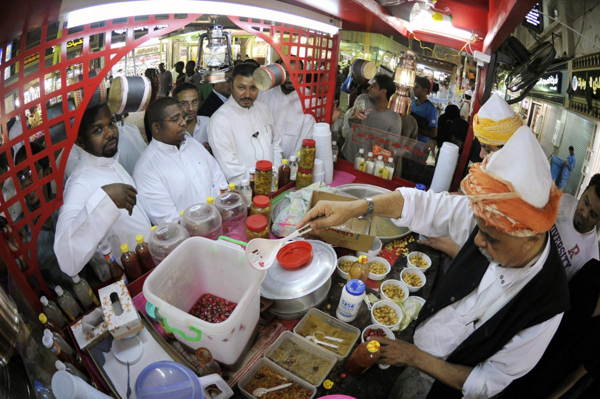 Men line up at a takeaway food stand in the Saudi port of Jeddah in the early hours of August 26, 2011. Practicing Muslims eat their suhoor meal before dawn during the holy fasting month of Ramadan.