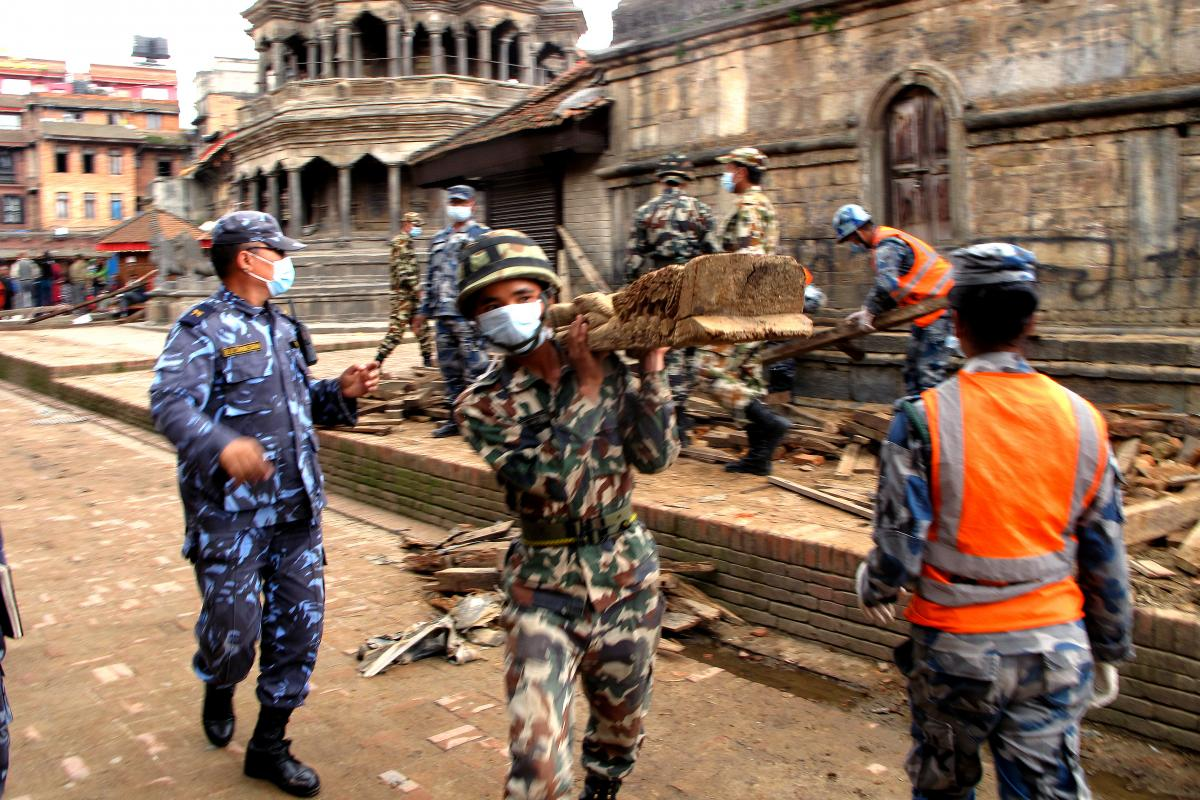 """Uniformed police move wooden beams, stack broken bricks and sift through ruined monuments --€"""" some of which date back to the 1600s --€"""" in the city of Patan in the aftermath of Nepal's massive earthquake."""