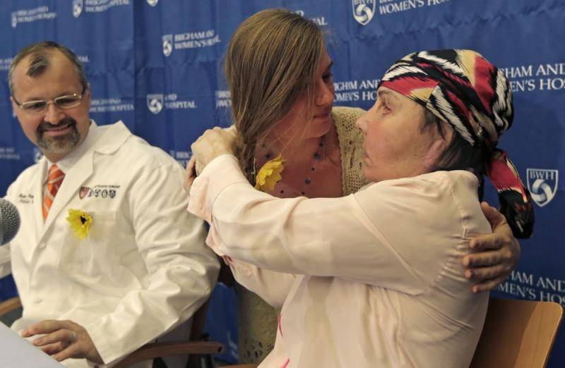 Carmen Blandin Tarleton of Thetford, Vermont, right, is embraced by Marinda Righter, daughter of face donor Cheryl Denelli-Righter, at Brigham and Women's Hospital in Boston, Mass., on Wednesday.