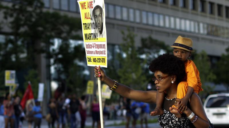 A woman, who refused to be identified, carries a young boy on her shoulders as she participates in a rally Sunday in Baltimore protesting the acquittal of George Zimmerman in the Florida shooting death of teenager Trayvon Martin.