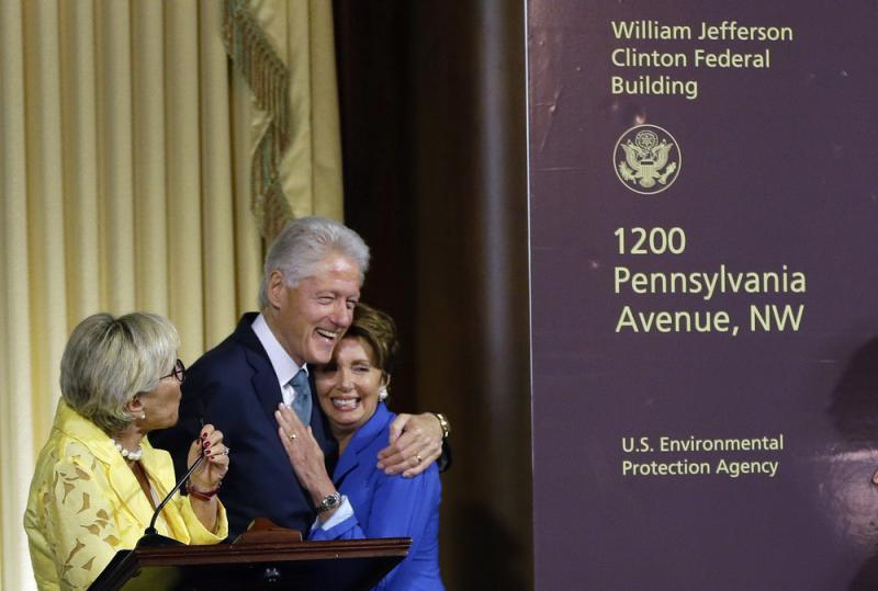Former President Bill Clinton hugs House Minority Leader Nancy Pelosi of California as another Democrat, Sen. Barbara Boxer of California, looks on at Wednesday's ceremony naming the Environmental Protection Agency headquarters for him.
