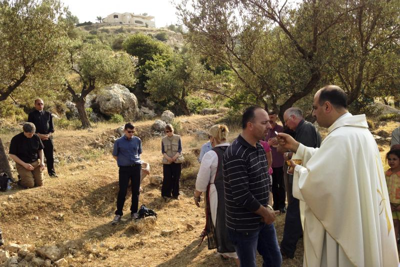 Ibrahim Shomali, a Palestinian priest, offers Communion under the olive trees of the Cremisan Valley in the Israeli-occupied West Bank. This is part of a regular protest against Israeli plans to build a section of its West Bank barrier here, which would s