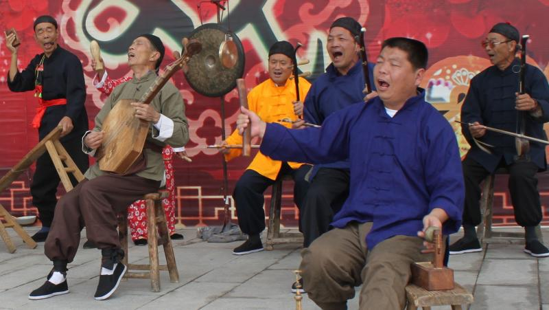 "Zhang Junmin (second from right) and his band perform the Lao Qiang music special in northwest China's Shaanxi province. The character behind the stage means ""drama""; Lao Qiang music used to accompany puppet plays and includes a strong storytelling compon"