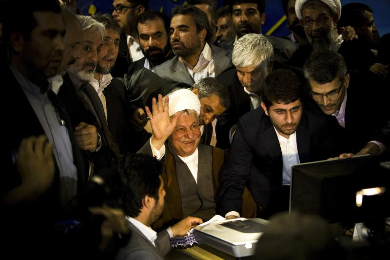 Former Iranian President Ali Akbar Hashemi Rafsanjani (center) waves as he registers his candidacy for the upcoming presidential election at the interior ministry in Tehran, May 11. Rafsanjani has been isolated since massive street protests in 2009 after
