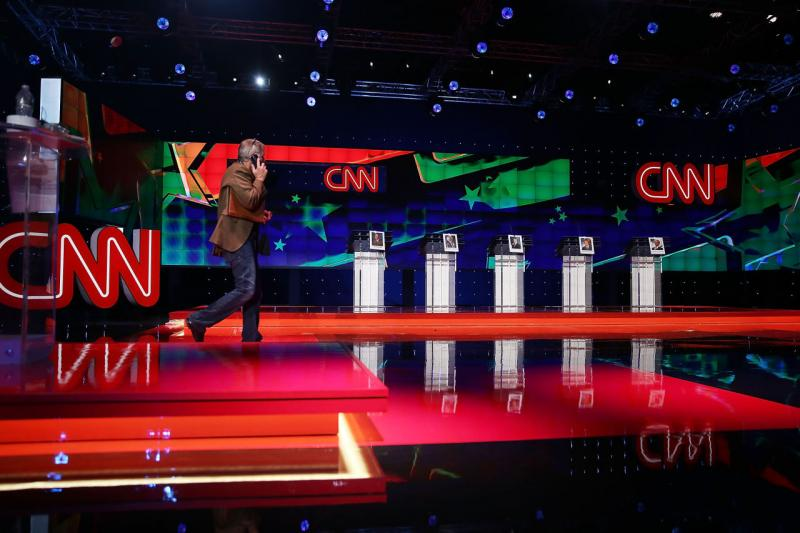 A person walks on the stage set up for the Democratic presidential candidates, former U.S. Sen. Jim Webb (D-VA), U.S. Sen. Bernie Sanders (I-VT), Hillary Clinton, Former Maryland Gov. Martin O'Malley and former governor of Rhode Island Lincoln Chafee, a d