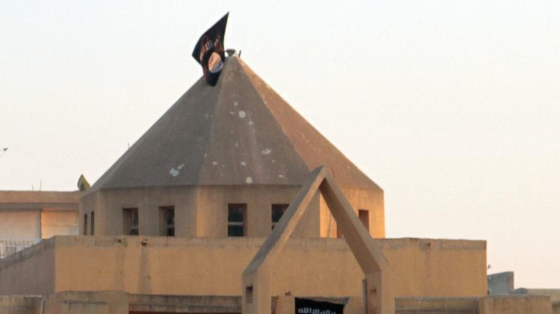 The flag of the Islamic State of Iraq and Syria, or ISIS, flutters on the dome of an Armenian Catholic Church in the northern rebel-held Syrian city of Raqqa on Sept. 28, 2013. At first, Syrian rebels and civilians welcomed the experienced Islamist fighte
