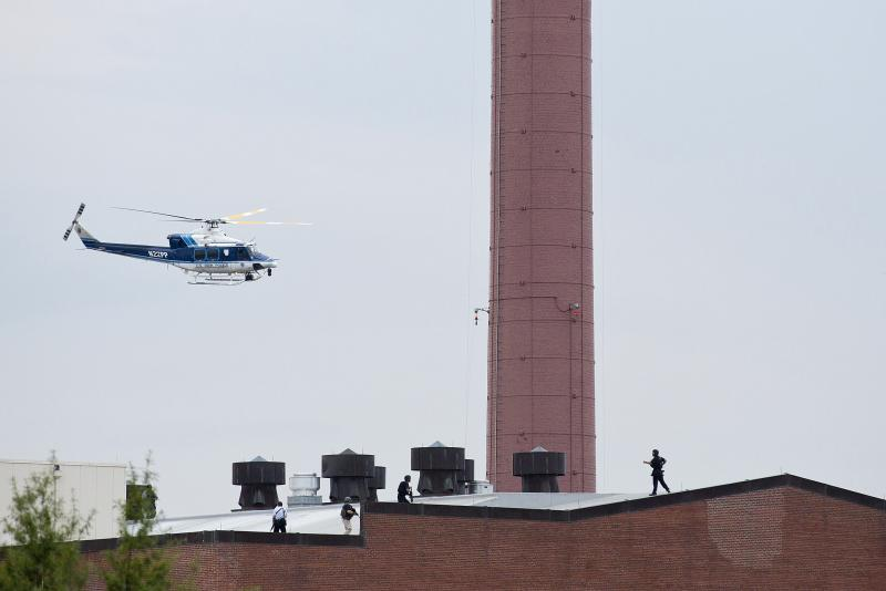 A police helicopter flies overhead as officers walk on the roof of a building.
