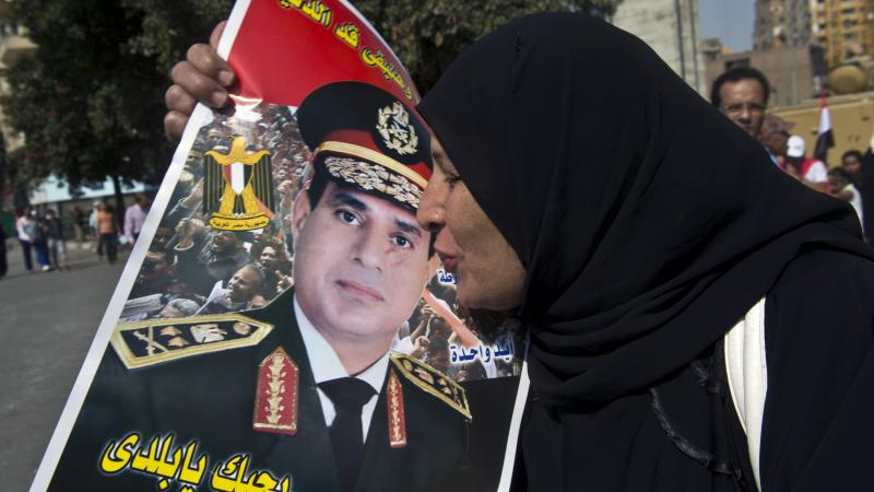 An Egyptian woman kisses a poster of Gen. Abdel-Fattah el-Sissi as she arrives at Cairo's Tahrir Square to mark the 40th anniversary of the 1973 Arab-Israeli war last month. Many are calling for the general to run for president next year, but so far he ha