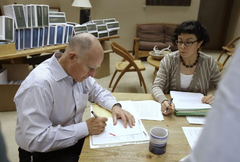 California Gov. Jerry Brown signs one of the hundreds of bills he has left to deal with as Graciela Castillo-Krings, right, his deputy legislative secretary, looks on at his Capitol office in Sacramento, Calif., Friday Oct. 9, 2015. (Rich Pedroncelli/AP)