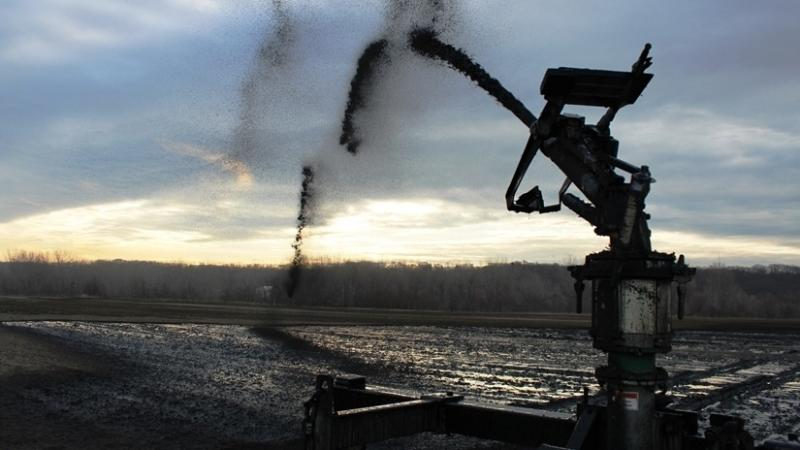 Thick jets of processed sewage arc out 30 to 40 feet from giant moving spreaders at Birmingham Farm in Kansas City, Mo.