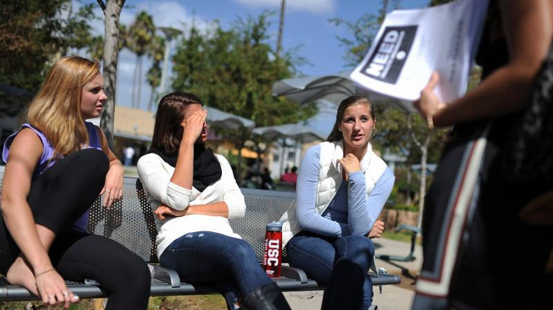 Students Amanda McComas, Rose Marie Chute and Sari Schwartz are approached in October at Santa Monica City College in California about signing up for insurance with the Affordable Care Act.