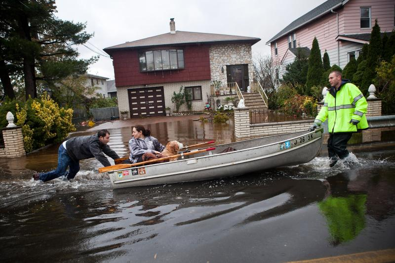 An emergency responder helps evacuate two people with a boat after their neighborhood in Little Ferry, N.J., was flooded.