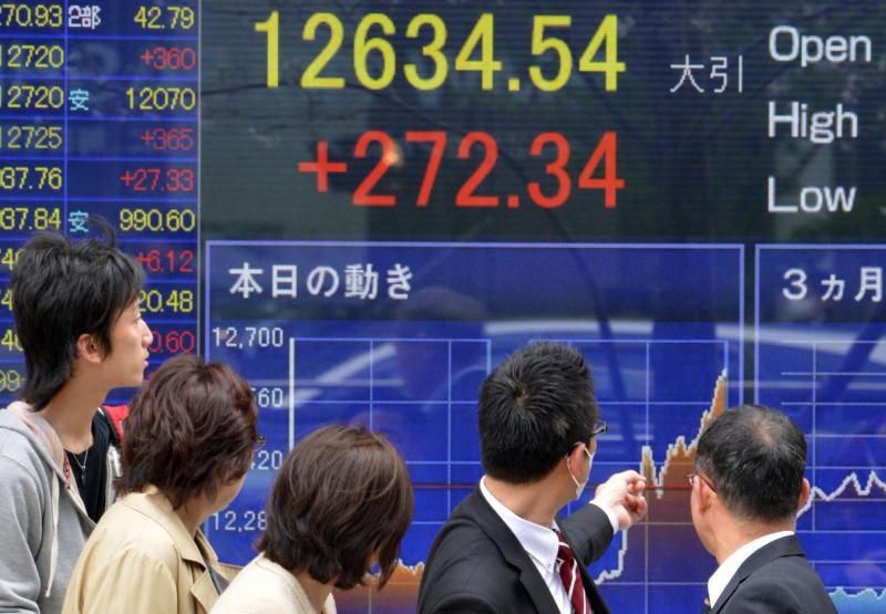Passersby watch share prices spike in Tokyo on April 4, the day Japan's central bank announced a massive purchase of government bonds. The bank hopes the scale of the effort will boost Japan's slow-moving economy.