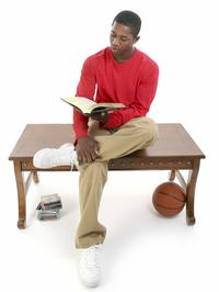 Casual man sitting on a table reading a book, with a stack of video games and a basketball nearby.