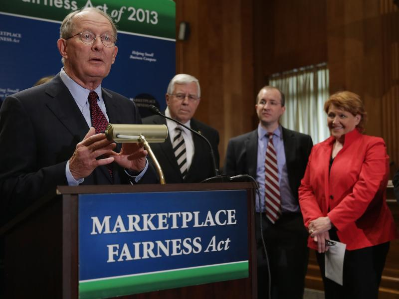 Sen. Lamar Alexander, R-Tenn. (left), leads a news conference about the Marketplace Fairness Act on Tuesday. The legislation would provide states with the authority to require out-of-state retailers to collect and remit taxes on purchases shipped into the
