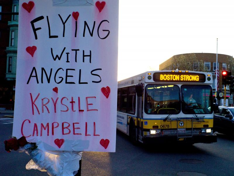 """A sign reading """"Flying With Angels Krystle Campbell,"""" is seen Monday as a passing MBTA bus with """"Boston Strong"""" displayed on its message board drives through Medford, Mass. A funeral service for Campbell, one of the three people killed in the marathon bom"""
