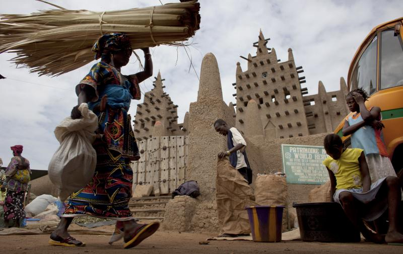 A woman walks by the Grand Mosque of Djenne on market day in Djenne, Mali, on Sept. 2. The UNESCO World Heritage-listed town is among the Malian tourist sites suffering from a huge drop in visitors after a coup took place in March and Islamist rebels seiz