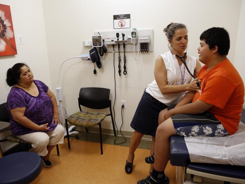 Families soon will be able to sign up for new health insurance options through the Affordable Care Act. In Washington, D.C., Dr. Cheryl Focht of Mary's Center performs a checkup of Jayson Gonzalez, 16, while his mother, Elizabeth Lopez, looks on.