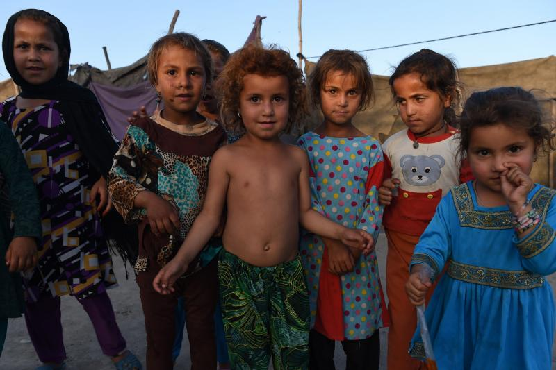 Afghan children look on at a refugee camp in Jalalabad on May 3, 2015. Like thousands of Afghan returnees, Neik Mohammad became unwanted in Pakistan after a Taliban massacre at a Peshawar school, forcing him to return home to a life of misery and fear in