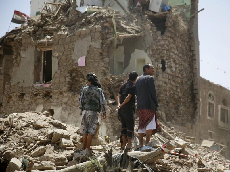 People stand amid the rubble of a house damaged by a Saudi-led airstrike last month in the old city of Sanaa, Yemen's capital.