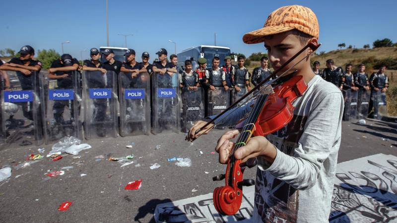 A refugee boy plays a violin as hundreds of migrants are blocked from marching down a highway toward Turkey's western border with Greece and Bulgaria on Saturday. Turkey has some 2 million refugees, mostly from Syria, but says they will not be allowed to