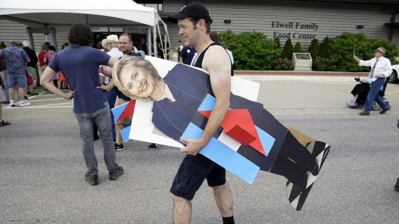 A man carries a cardboard cutout of Hillary Clinton in Des Moines, Iowa. Clinton and other traditional candidates have struggled to breakthrough as outsiders have captured the attention this summer.