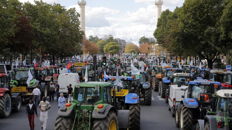 Upset over falling prices on their goods, angry farmers park their tractors as they protest in Paris on Thursday.