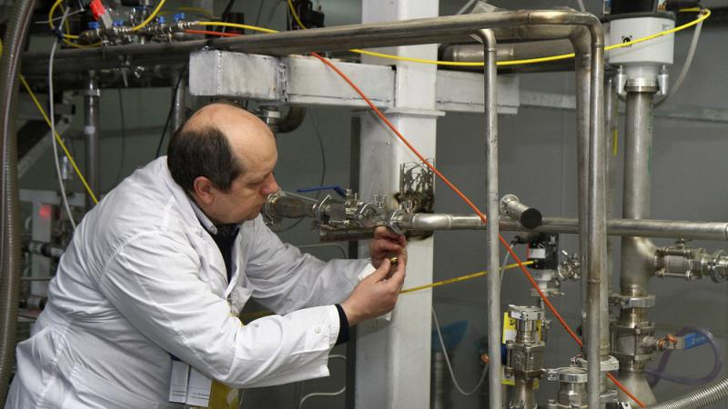 An International Atomic Energy Agency inspector cuts a uranium enrichment connection at Iran's Natanz facility, 200 miles south of Tehran, in 2014. The U.S. Congress is expected to address the Iranian nuclear deal this month. One unresolved issue: How muc