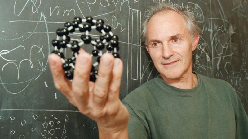 Harry Kroto, pictured in 1996, displays a model of the geodesic-shaped carbon molecules that he helped discover.