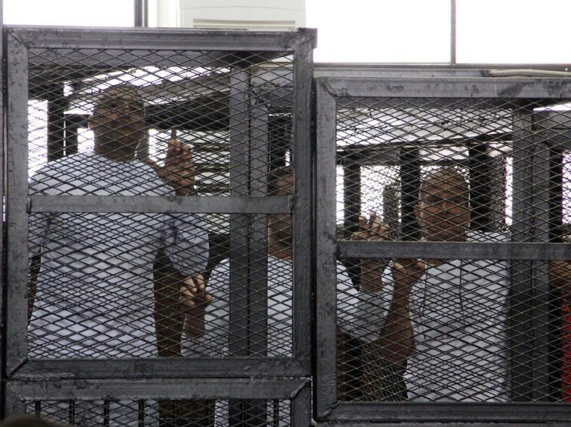 Al-Jazeera English journalists Mohammed Fahmy, left, Baher Mohamed, center, and Peter Greste, right, appeared in a cage during their trial on terrorism-related charges in Cairo in March 2014. The journalists denied all charges. Greste, an Australian, was