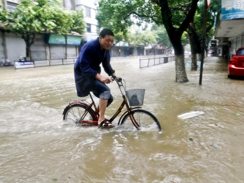 A resident rides a bicycle on a road submerged by water in Xiangshan county, east China's Zhejiang Province, on Saturday after Typhoon Chan-hom hit the Chinese coast south of Shanghai, forcing 1.1 million people to evacuate.