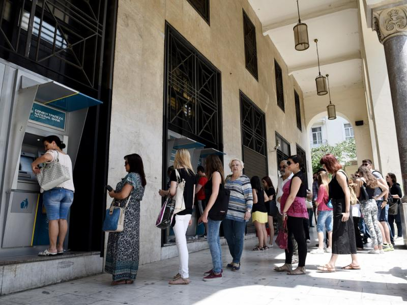 People stand in a line to use the ATMs of a bank in the northern Greek city of Thessaloniki on Saturday after the country's prime minister announced a snap referendum on an international bailout — pushing Athens toward a Tuesday deadline for a plan t