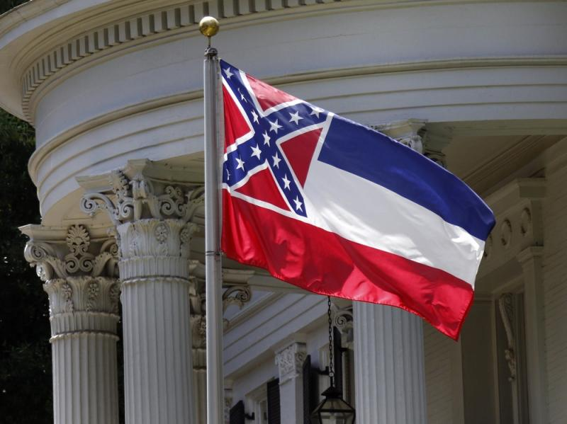 The state flag of Mississippi is unfurled against the front of the Governor's Mansion in Jackson, Miss., on Tuesday. The flag has been the center of renewed controversy since last week's racially motivated shooting of nine parishioners at a black church i