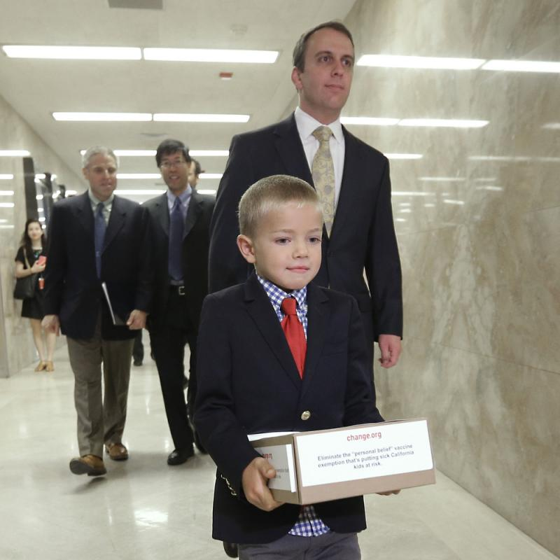 Leukemia survivor Rhett Krawitt, 7, carries a box of petitions representing more than 30,000 people supporting a measure requiring nearly all California schoolchildren to be vaccinated. He took them to the governor's office at the Capitol in Sacramento, C