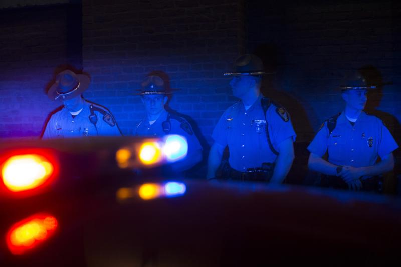 Police officers are illuminated by patrol car lights during a protest against the acquittal of Michael Brelo on Saturday in Cleveland.